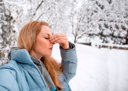 Blonde Woman holding her Nose outside in snowy winter day. Suffering from nasal sinus problems on cold weather.Copy space