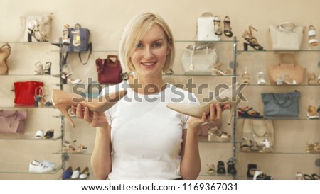 Blonde woman holding light beige and dark beige shoes. She looks at them, then shrugs and smiles at camera. Woman is in shoe shop #1169367031
