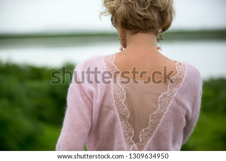 Blonde woman in baby pink mohair sweater with lace trim