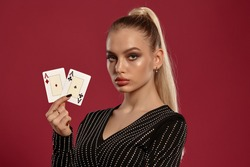 Blonde woman in black dress in rhinestones. Showing two playing cards, posing against red background. Gambling entertainment, poker, casino. Close-up
