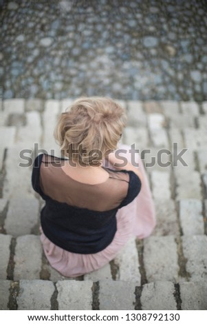 Blonde woman in black mohair sweater and pink skirt sitting on stairs