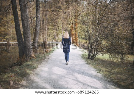 Blonde woman in blue elegant coat walks alone in the sunny seasonal park with lake and trees. #689124265