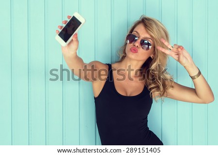 blonde woman in bodysuit with perfect body taking selfie with smartphone  toned instagram filter