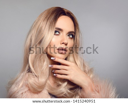 Blonde woman in glamorous fur coat posing in studio. Ombre blond hairstyle. Beauty fashion girl portrait. Beautiful model with makeup, long healthy hair style. Manicured nails.