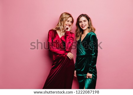 Blonde woman in long velvet dress looking at her sister. Smiling charming girls posing on pink background.