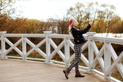 Blonde woman in red beret, black jacket, checkered trousers is taking photos using her smartphone outdoors in the park in autumn.