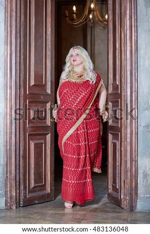 Blonde woman in red dress stands in doorway, holding doors handles.