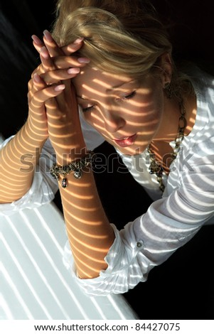 Blonde woman in the sunlight looking through jalousie leaning her elbows on windowsill - stock photo