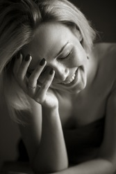 Blonde woman laughs, covering her face with her hand. Emotion concept