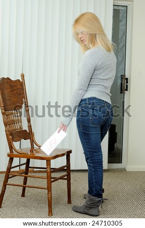 Blonde woman leaving good-bye note on chair in empty apartment