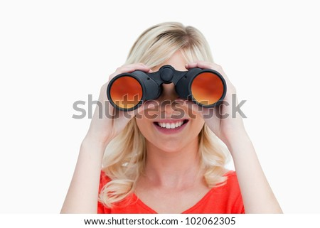 Blonde woman looking through binoculars against a white background - stock photo