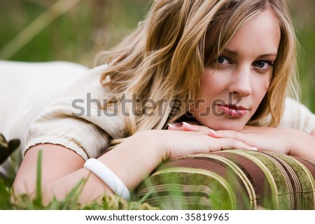Blonde Woman lying on the grass on her stomach with a pillow
