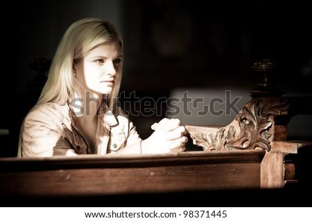 Blonde Woman Praying inside of a Church