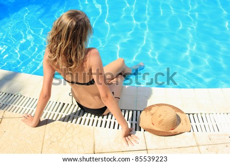 Blonde woman relaxing by the pool