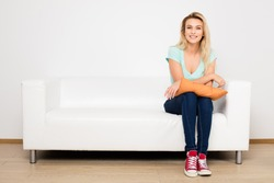 blonde woman sitting on her white sofa with pillow in hands