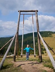Blonde woman sitting on seat and putting hands on two support of giant street swing made from wooden frame, on background of mountain hill covered with trees.