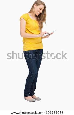 Blonde woman smiling while using a touch pad against white background