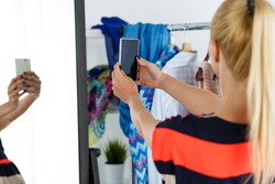 Blonde woman standing near wardrobe rack full of clothes and mirror making selfie with cellphone in new dress. Shopping and consumerism or stylist concept. Nothing to wear and hard to decide concept