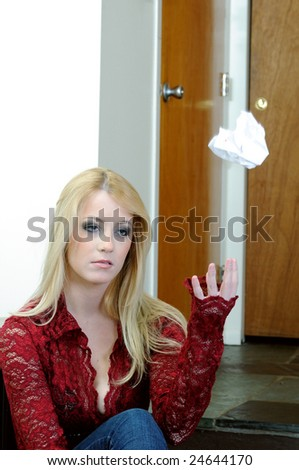 Blonde woman tossing wadded up note in air