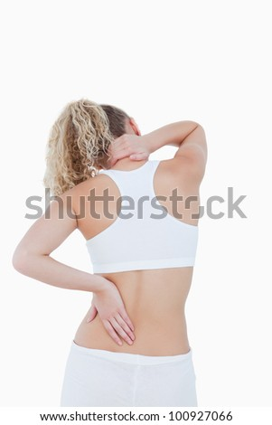 Blonde woman touching her painful neck and back against a white background