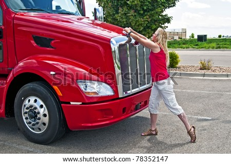 Blonde woman truck driver opening the hood on a semi-truck. - stock
