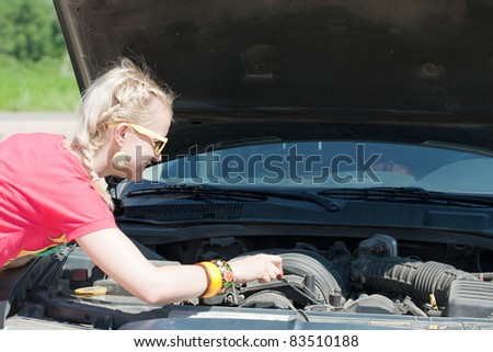 Blonde woman trying to fix the car