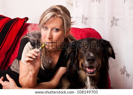 Blonde woman with a dog smoking a e cigarette