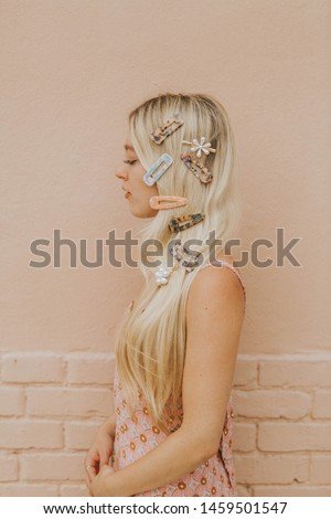 Blonde Woman with Acrylic and Pearl Clips in her hair, model wearing resin hair barrettes, modern hair pins on girl, pink brick wall background