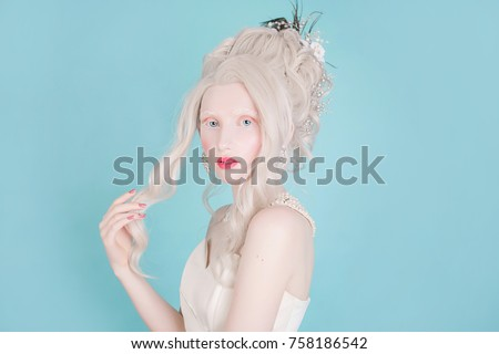 Stock Photo Blonde woman with beautiful luxurious rococo hair style in white dress on a blue background