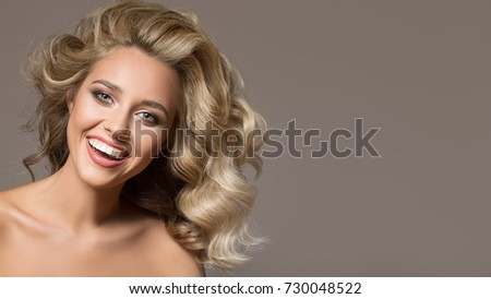 Blonde woman with curly beautiful hair smiling on gray background.  #730048522