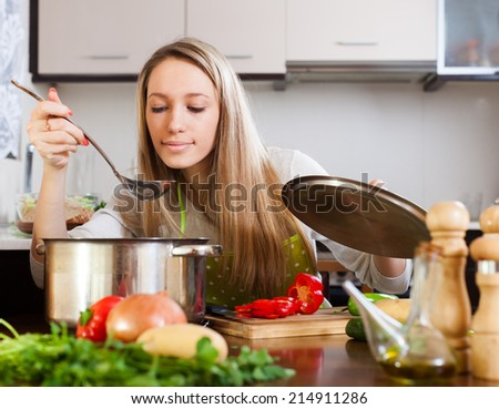 Blonde woman with ladle cooking soup in home kitchen