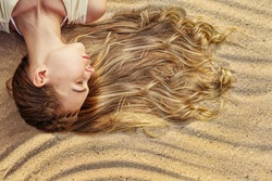 Blonde Woman with Long Wavy Hair on the Sea Sand. Natural Hair Care Cosmetics, Sun Bath in Tropic