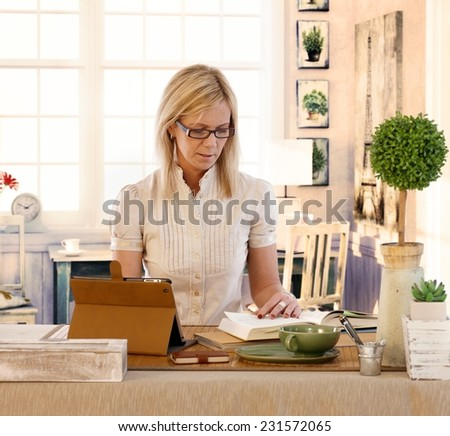 Blonde woman working at home, using tablet, reading book.