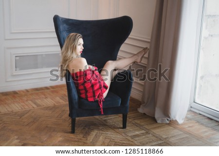 Stock Photo Blonde young bare shoulders red plaid lipstick nails underwear sitting on chair looking out window posing beautifully exciting. Day, light vacation vintage old french style. Copy space.