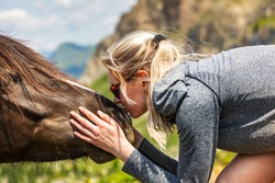 Blonde young female animal lover kissing a wild horse on its nose