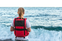 Blonde young girl in life jacket stands on the beach and watching waves. Lifeguard woman coast guard in bright red life vest looks in open sea. Ocean Shore Security Concept. Rough seas. View from back