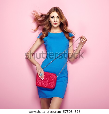 Blonde young woman in elegant blue dress. Girl posing on a pink background. Jewelry and hairstyle. Girl with red handbag. Fashion photo #575084896
