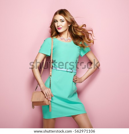 Blonde young woman in elegant green dress. Girl posing on a pink background. Jewelry and hairstyle. Girl with handbag. Fashion photo