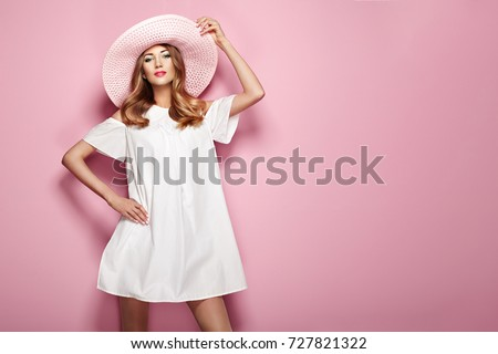 Blonde Young Woman in elegant white Dress and Summer Hat. Girl posing on a Pink Background. Jewelry and Clothing. Fashion photo #727821322