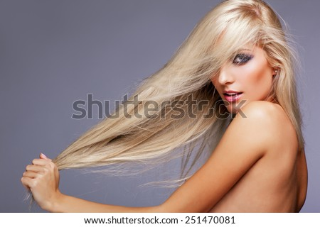 Blonde young woman on gray background