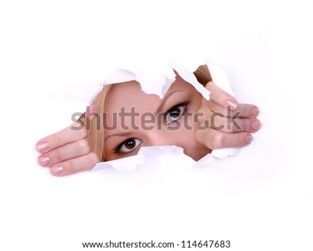 blonde young woman peeping through hole on paper