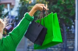 Blonde young woman wearing green sweater and standing with her back to camera holding vibrant shopping bags in a raised hand. Black Friday sales