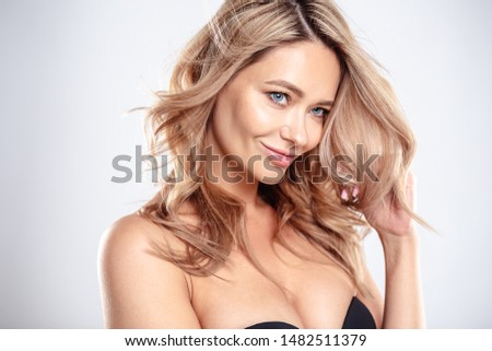 Blonde young woman with healthy curly hair and natural make up . Beautiful model girl with wavy hairstyle. Care and beauty #1482511379