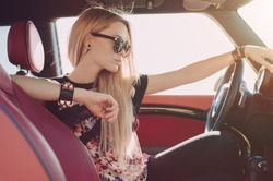 Blondie young girl at the wheel of sport car with red interior with black sunglasses and black leather armlets with metal inserts seating sideward and looking at the road