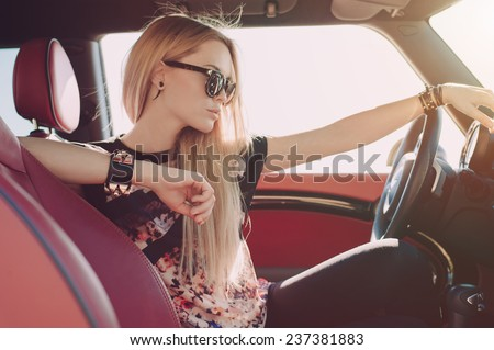blondie young girl at the wheel of sport car with red interior with black sunglasses and black. Black Bedroom Furniture Sets. Home Design Ideas