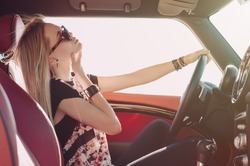 Blondie young girl at the wheel of sport car with red interior with black sunglasses and leather armlets seating sideward with hand near her check and wind in her hair and looking at the road