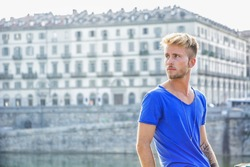 Blondish, blue eyed young man by river at sunset in downtown Turin, Italy, looking away to a side