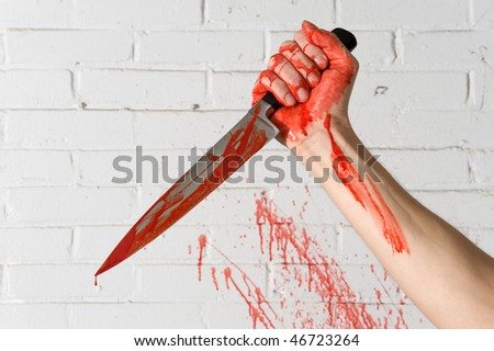 stock photo : Blood covered knife, still dripping, in the hands of a