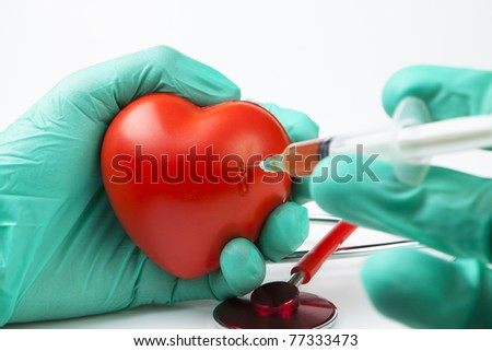 blood drop while injecting red heart with syringe with two hands green gloves