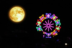 Blood moon on night sky and colorful light on Ferris wheel, Elements of this image furnished by NASA